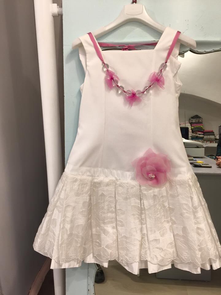 un abito da bambina di color bianco con una collana di color rosa
