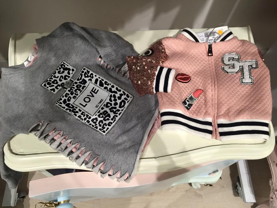 una maglia di color nero e una felpa di color rosa da bambina