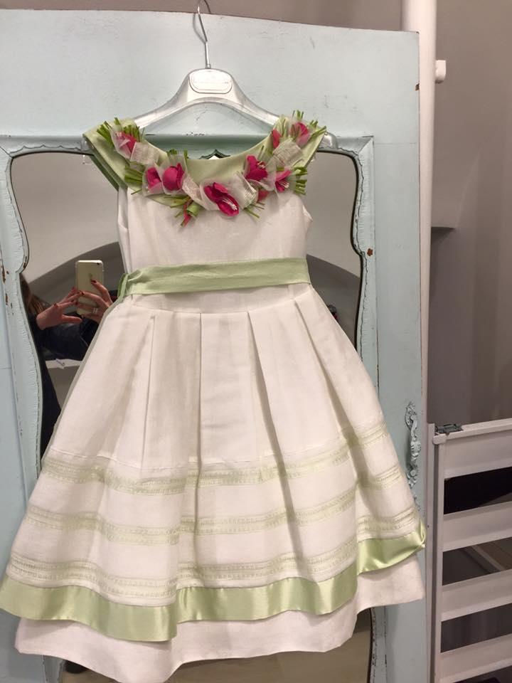 un abito di color bianco e verde con disegni a fiori fucsia