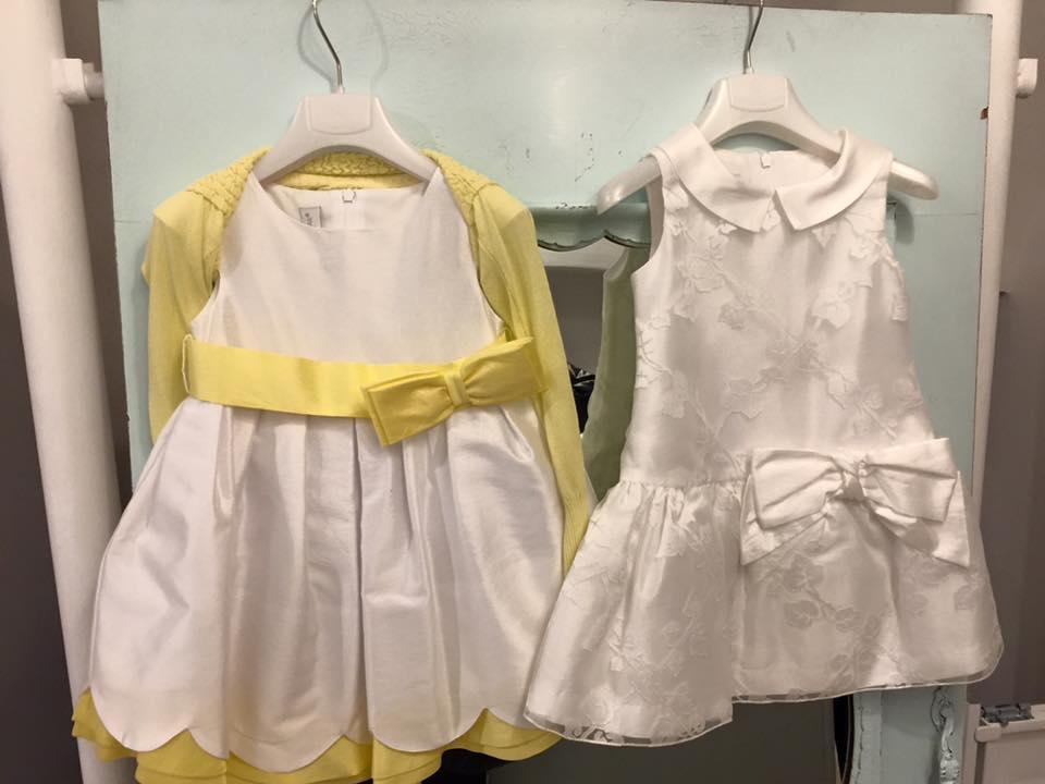 due abitini di color bianco con dei fiocchi