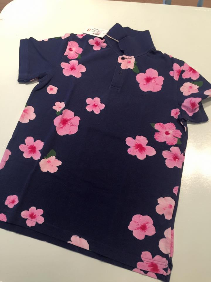 una maglietta da bambino di color blu con disegni a fiori di rosa