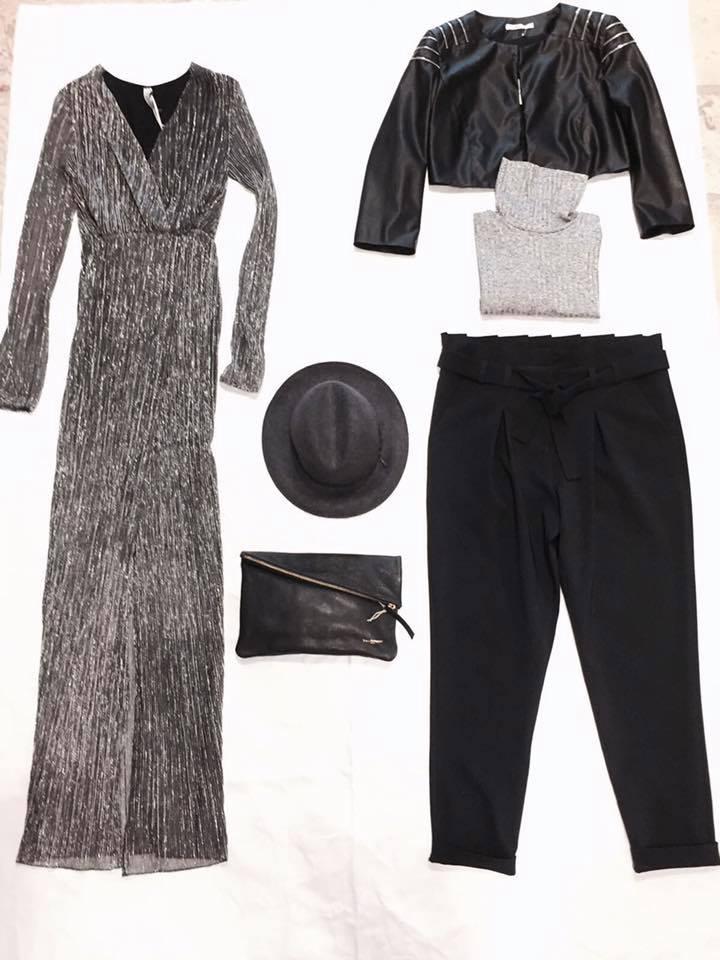un abito grigio e accanto un paio di pantaloni, una giacca di pelle e un cappello di color nero