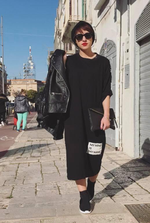 una ragazza con un abito nero e una giacca di pelle
