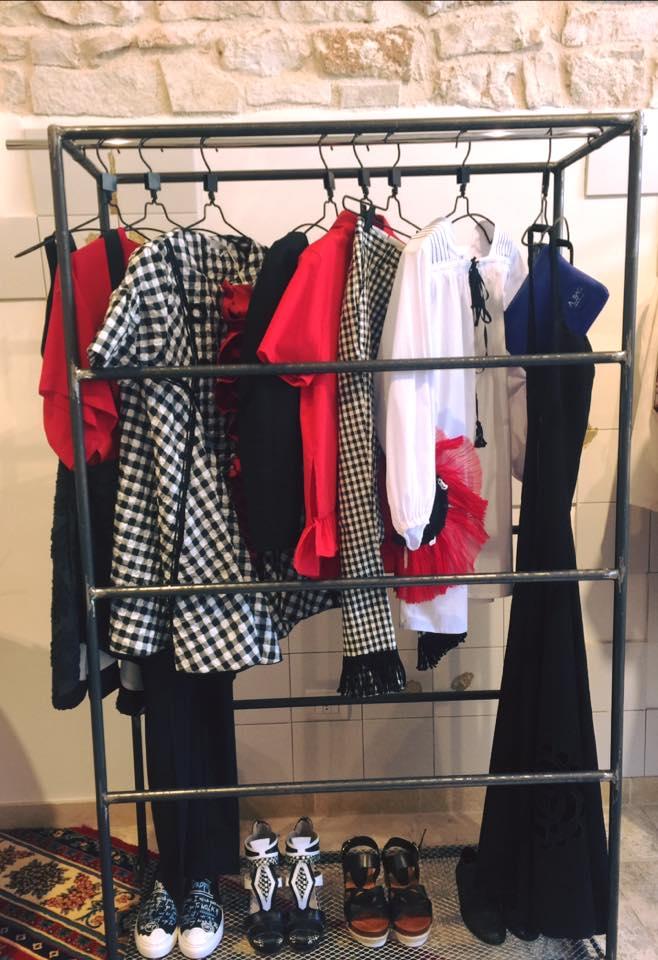 un appendino con delle camicie di color bianco, rosso e con disegni a scacchi