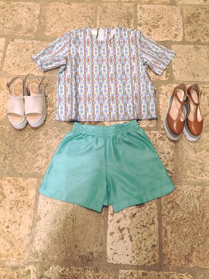 un paio di pantaloncini di color verde e una camicetta di color azzurro e marrone