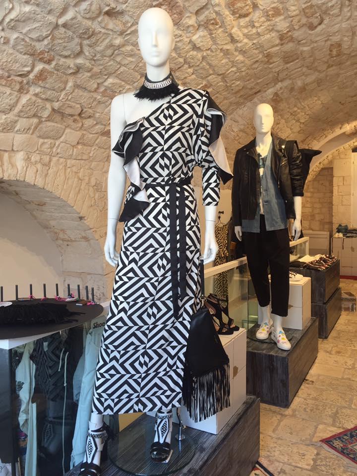 due manichini in una boutique con un abito di color bianco, nero e una giacca di pelle da uomo
