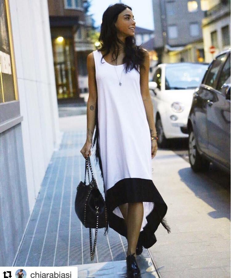una donna con un abito di color bianco con bordi neri
