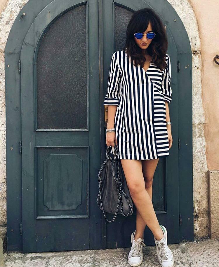 una donna con un abito a righe di color bianco e nero e una borsa di pelle in mano