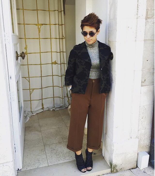 una donna con un paio di pantaloni marroni, una maglia grigia e una giacca