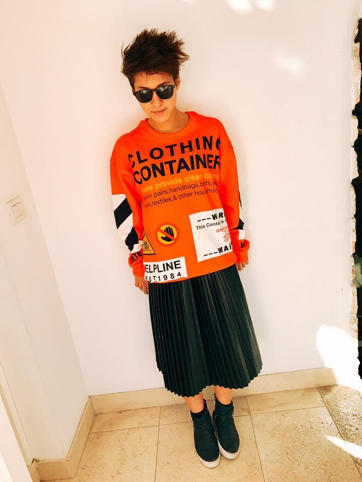 una donna con una gonna a plissé nera e una maglia arancione con scritto Clothing Container