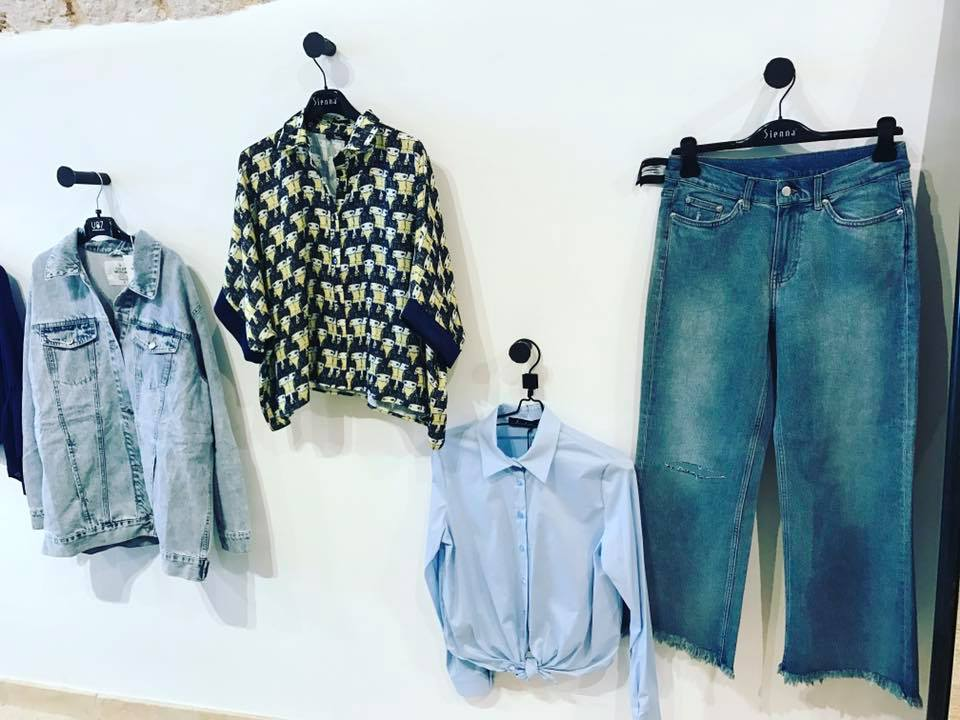 due camicie, una giacca e un paio di jeans appesi