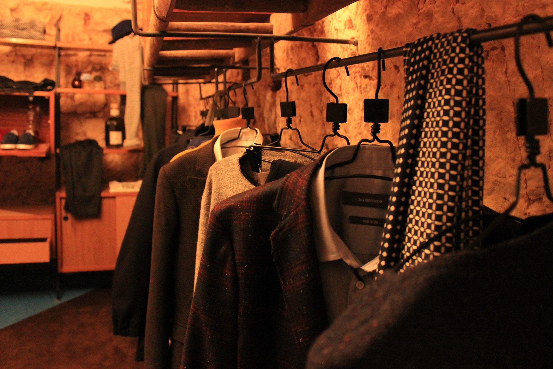 un appendino con delle maglie, camicie e giacche di lana