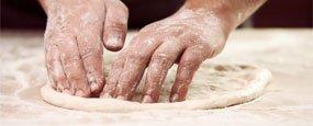 mani che impastano una pizza