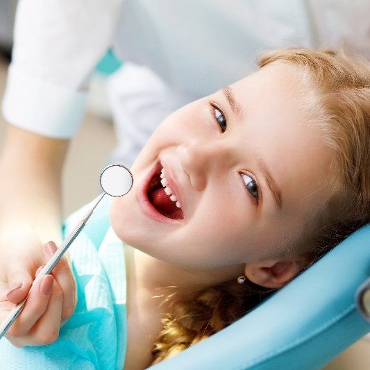 Small girl has her teeth examined, and smiles throughout