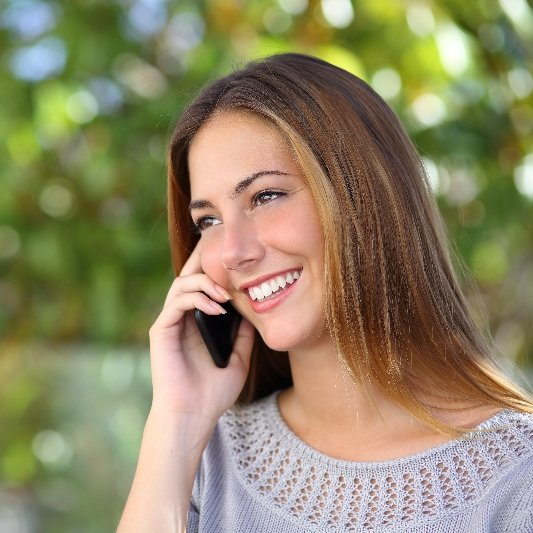 Woman speaks on telephone, making an appointment with a dentist