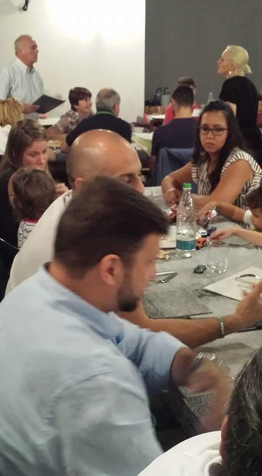 un uomo con un bambino seduto a tavola con una torta di compleanno