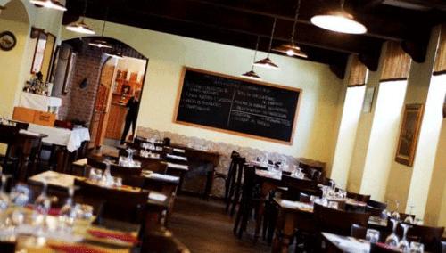 Vista del ristorante, nella parete una grande lavagna con il menu