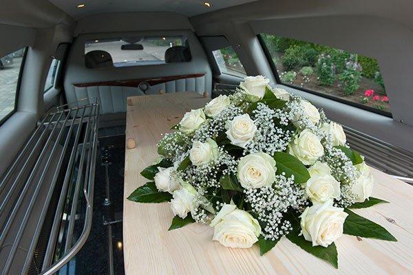 una bara con un bouquet di fiori bianchi sopra in un carro funebre