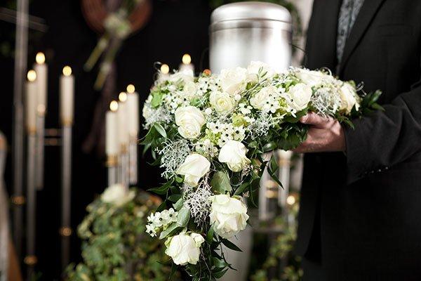 una mano con una composizione di rose bianche