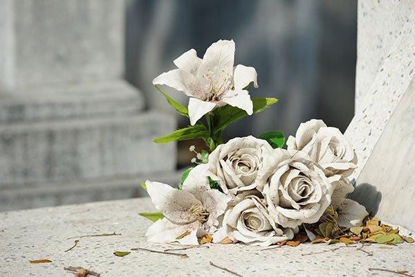 Vecchio fiore bianco falso sulla tomba