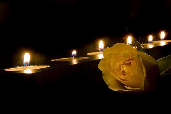 Scena con una rosa gialla e candele accese