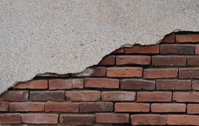 cracked plaster exposing brickwork