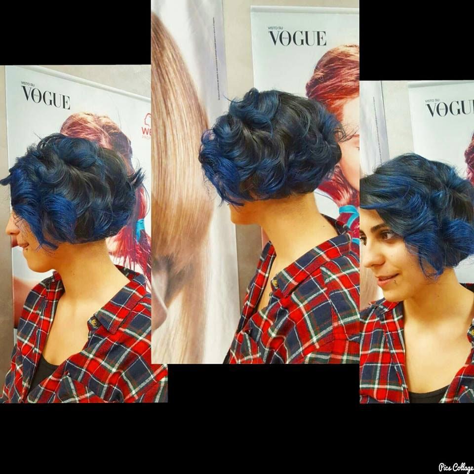 una ragazza con una camicetta scozzese rossa e blu e un taglio di capelli corti e mossi di color blu e nero