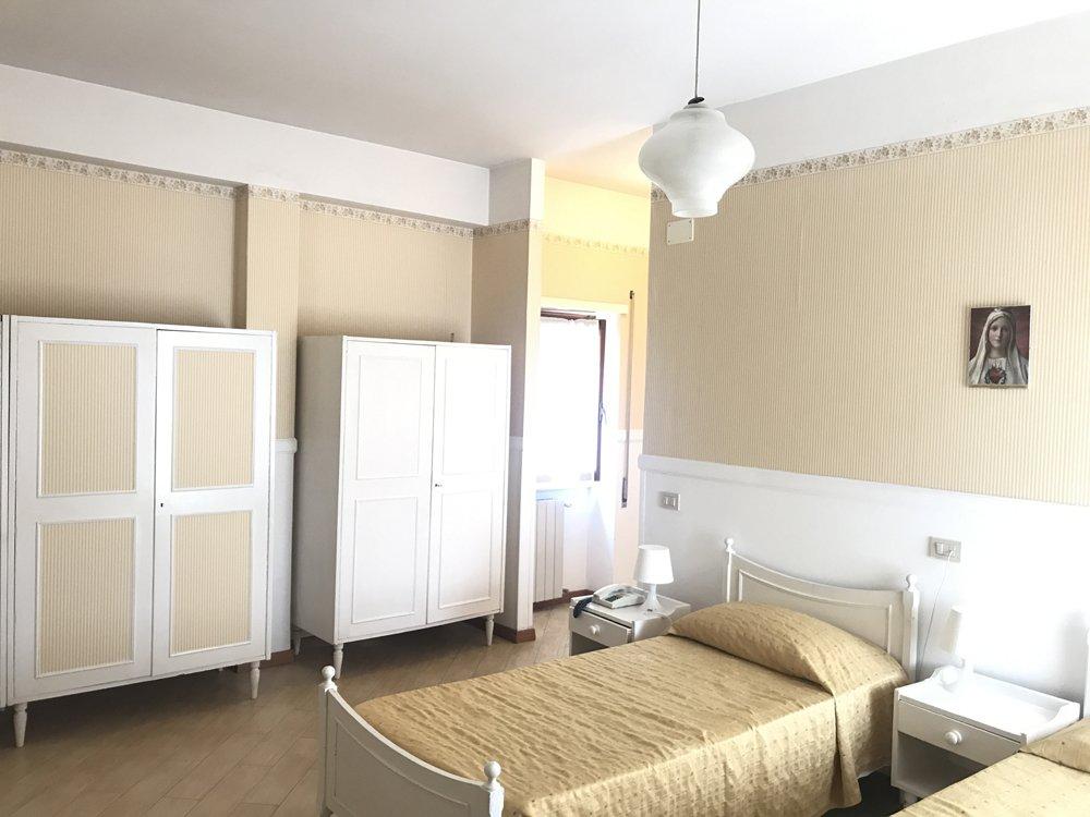 stanza singola con letto e armadi bianchi