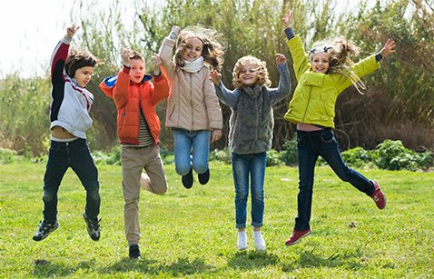 Group of children in high spirits jumping outdoors