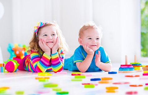 Preschooler children playing with colorful toy blocks