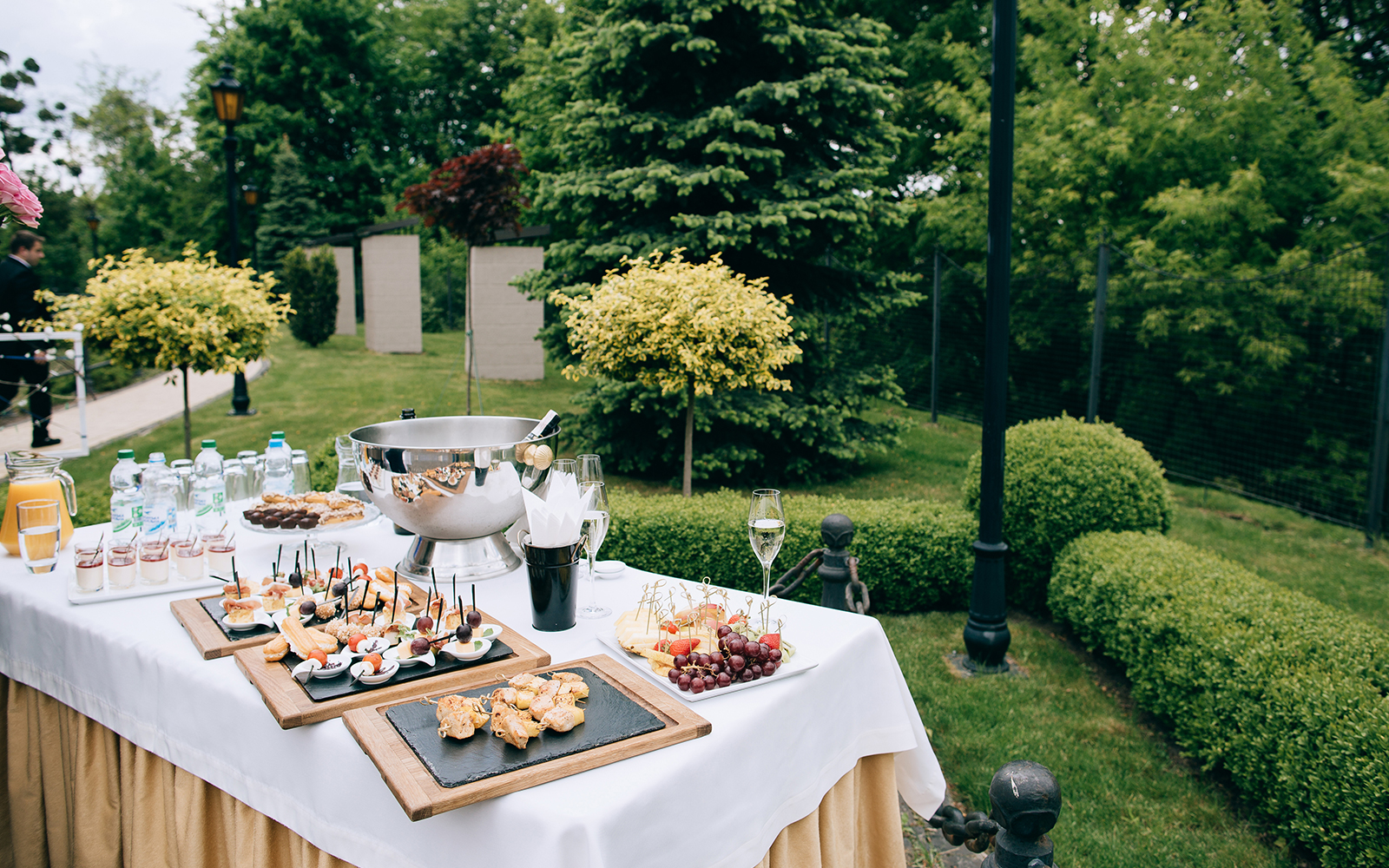 un tavolo apparecchiato in un giardino con tartine, frutta, bottiglie d'acqua e altro