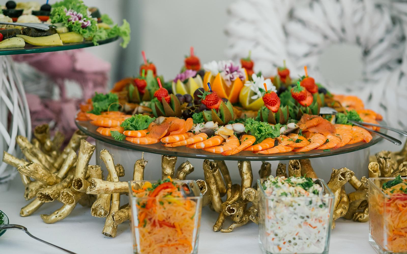 dei gamberi, decorazioni con frutta e verdura e altri antipasti
