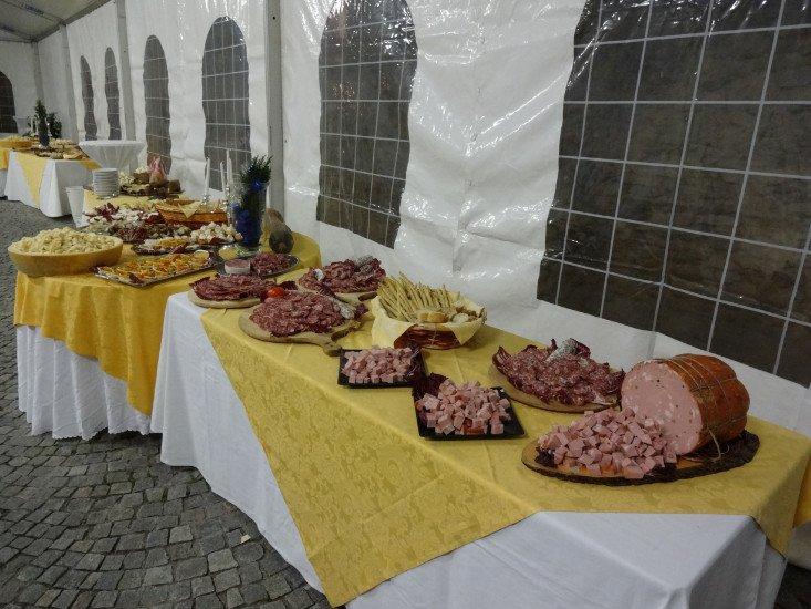 una tavolata all'aperto con fette di mortadella a cubetti dentro a dei piatti, dei grissini e altre specialità