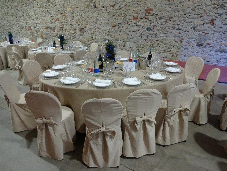 una tavola rotonda con una tovaglia beige apparecchiata per un ricevimento