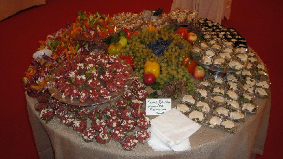 un tavolo con sopra della tartare di carne dentro a delle coppette,verdura, frutta  e dessert