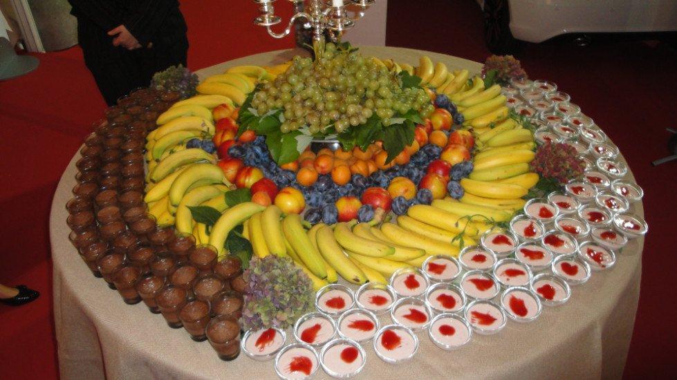 un tavolo con sopra delle coppette di dessert,banane, prugne,pesche, arance e uva