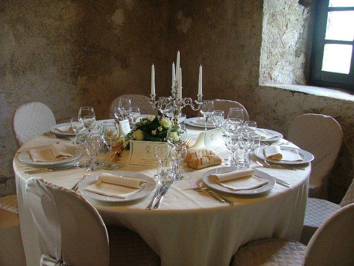 un tavolo apparecchiato per un evento con un bouquet di rose bianche