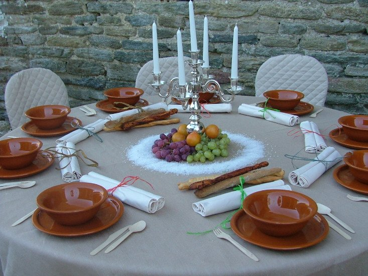 un tavolo apparecchiato con delle ciotole marroni e al centro un candelabro e della frutta