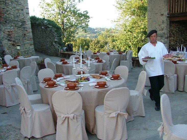 dei tavoli apparecchiati per un ricevimento all'esterno e un cameriere con una coppola in testa con dei piatti in mano