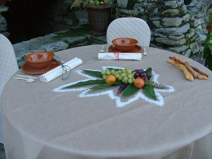 un tavolo apparecchiato con due ciotole dei grissini e della frutta appoggiata su una foglia