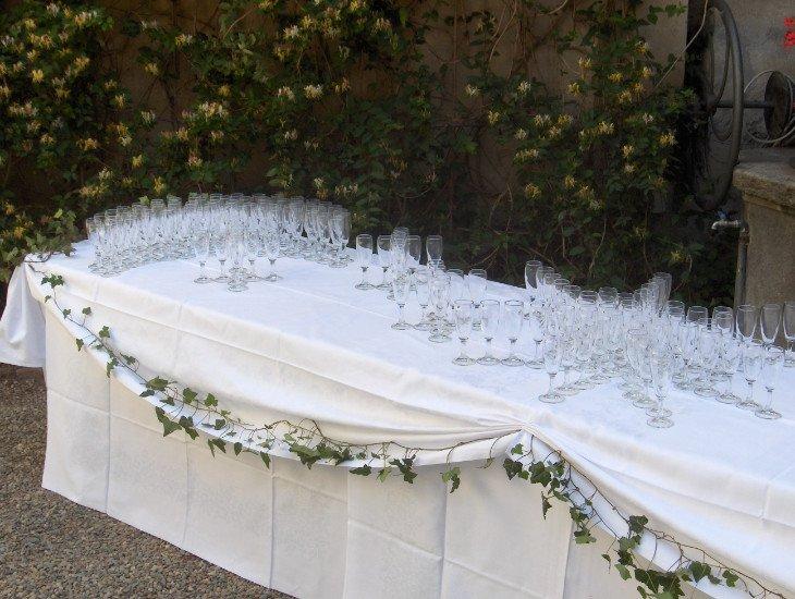 una lunga tavolata con sopra dei bicchieri e dell'edera rampicante