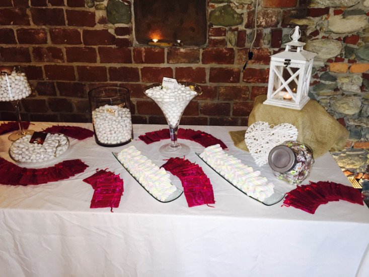 un tavolo con dei barattoli di confetti, marashmallow e dei tovagliolini bordeaux