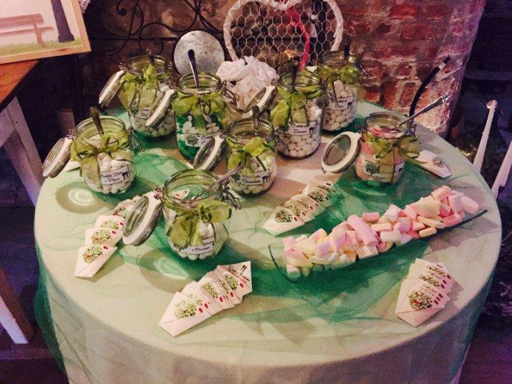 un tavolo con dei vasetti con sopra dei barattoli con dei confetti con un nastro verde e dei marshmallow