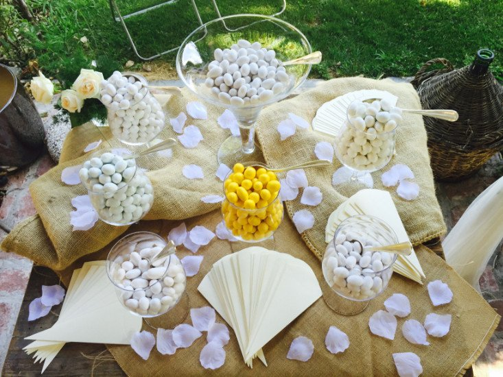 dei sacchi in iuta con dei petali e sopra e dei barattoli con dei confetti