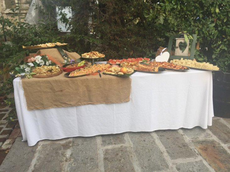 un tavolo con sopra dei vassoi con delle tartine e degli