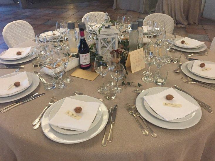 un tavolo apparecchiato con delle noci nei piatti e una bottiglia di vino