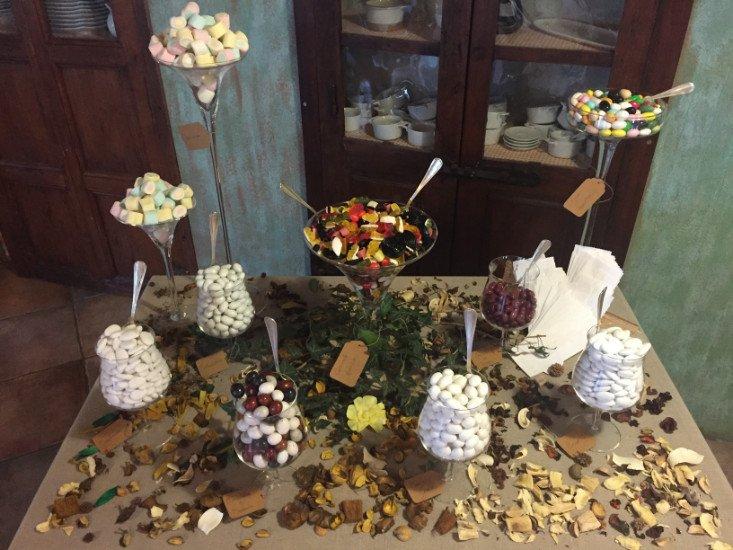 un tavolo con sopra dei barattoli di confetti, marshmallow e della frutta secca sparsa