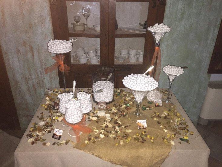 un tavolo con dei barattoli di confetti e della frutta secca sparsa per il tavolo