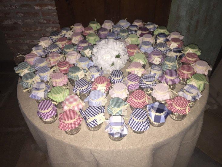 un tavolo con sopra dei barattoli con dei tappi a righe di diversi colori e al centro un bouquet di fiori bianchi