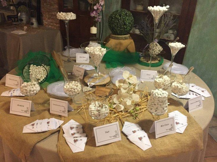 un tavolo con dei sacchi in iuta e sopra dei barattoli di confetti e biglietti d'invito